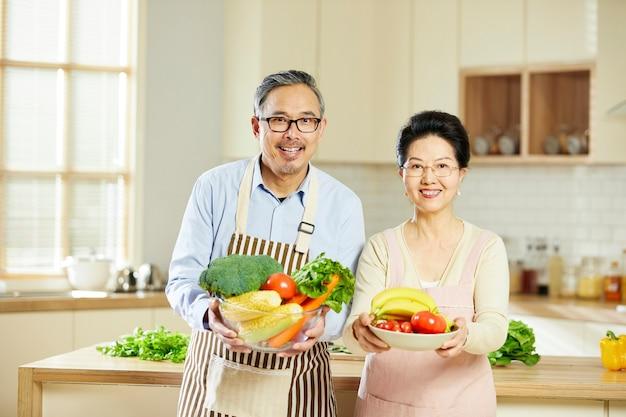 Portret van een oud getrouwd stel staat vrolijk in de keukenkamer