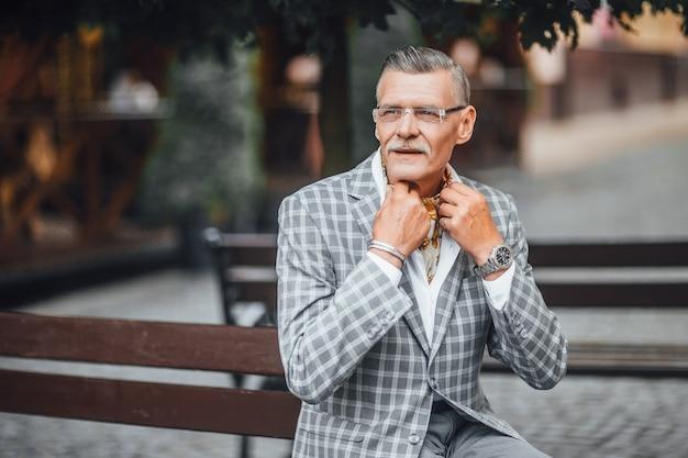 Portret van een oude bebaarde man in grijze jas die de armen kruist terwijl hij ernaar uitkijkt en glimlacht. kopieer de ruimte aan de linkerkant