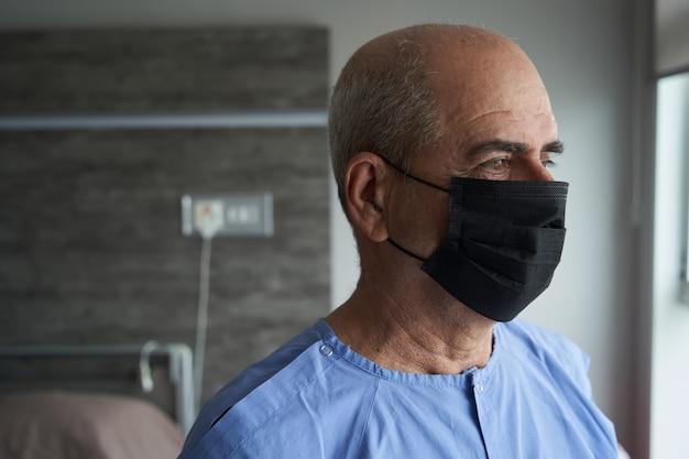 Portret van een oude man, 70 jaar oud, in een medisch masker