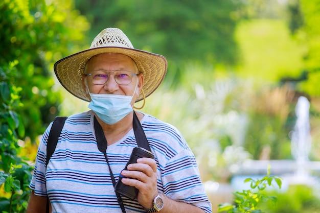 Portret van een oude man die een medisch masker draagt tijdens het coronavirus in een park