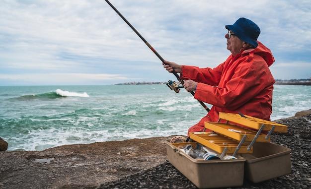 Portret van een oude man die in de zee vist. visserij concept.