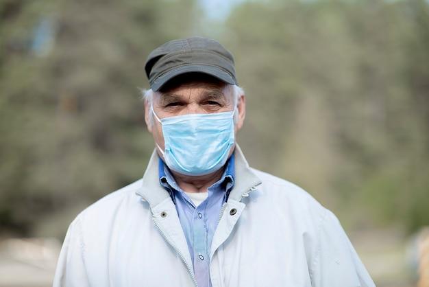 Portret van een oude man met een medisch masker. een concept van het gevaar van coronavirus voor ouderen.