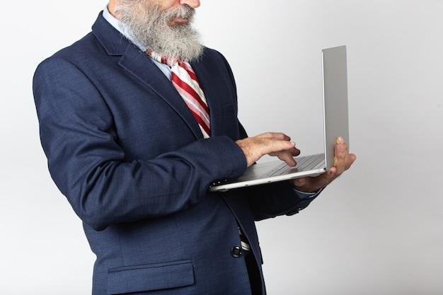 Portret van een oude man met een pak en een baard die op internet op een laptop surft. lifestyle concept, technologie. geïsoleerd op witte achtergrond.