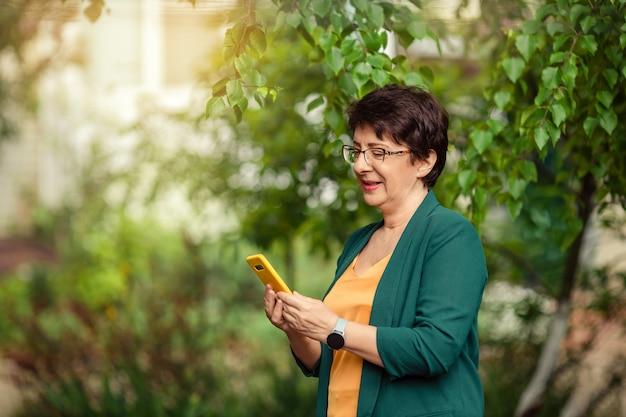 Portret van een oude stijlvolle grootmoeder in glazen met een mobiele telefoon in haar handen op de natuur.