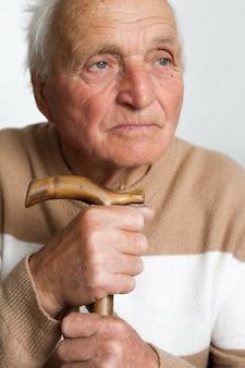 Portret van een oude, trieste man die zijn hoofd op het handvat van een houten wandelstok legde.