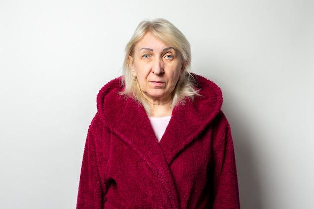 Portret van een oude vriendelijke vrouw in een casual jas op een geïsoleerde lichte muur. emotioneel gezicht
