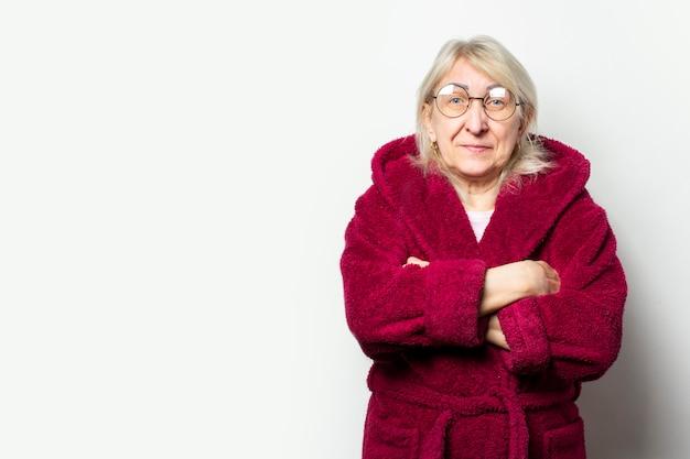 Portret van een oude vriendelijke vrouw in een casual kamerjas en bril met armen gekruist op haar borst op een geïsoleerde lichte muur. emotioneel gezicht