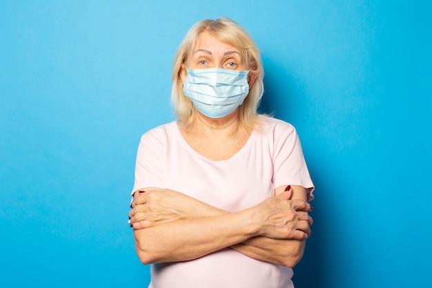 Portret van een oude vriendelijke vrouw in een t-shirt en een medisch beschermend masker sloeg haar armen over haar borst tegen een blauwe muur. emotioneel gezicht. conceptvirus, quarantaine, vuile lucht, pandemie