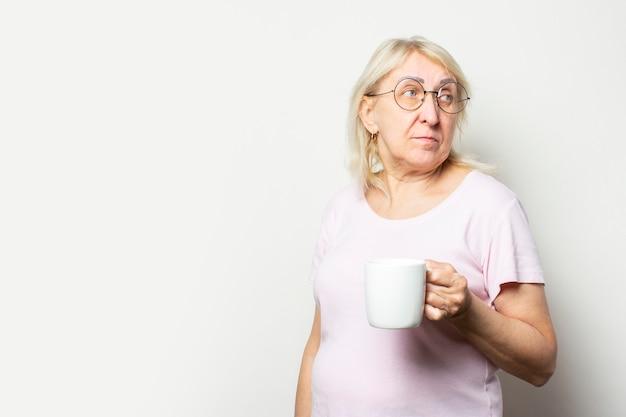 Portret van een oude vriendelijke vrouw met een glimlach in een casual t-shirt en een bril houdt een mok in haar handen en kijkt terug op geïsoleerde lichte muur. emotioneel gezicht. 's ochtends koffie concept, ontbijt