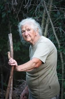 Portret van een oude vrouw die met artritische voeten door het bos loopt dat op een stok als riet leunt