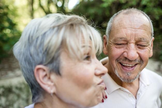 Portret van een ouder echtpaar waar de man lacht om de grimas van zijn vrouw tijdens een wandeling op het platteland.