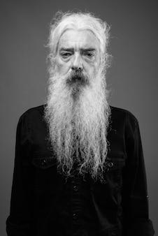 Portret van een oudere bebaarde man met een zwart shirt op grijs in zwart-wit