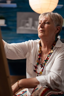 Portret van een oudere kunstenaar die een meesterwerk maakt