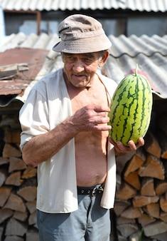 Portret van een oudere man die een watermeloen vasthoudt