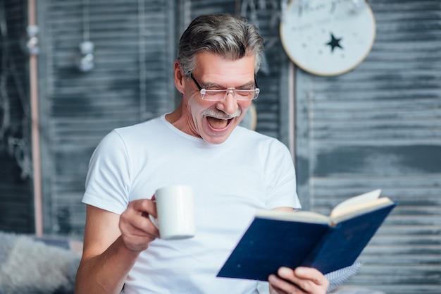 Portret van een oudere man die op bed zit, een boek vasthoudt en vrolijk glimlacht