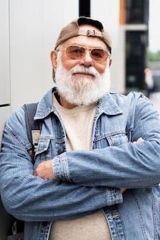 Portret van een oudere man die zich voordeed terwijl hij buiten in de stad was