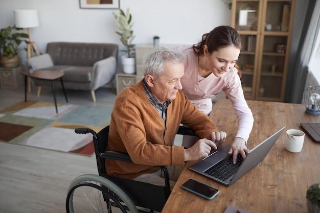 Portret van een oudere man in een rolstoel die een laptop gebruikt in het bejaardentehuis met een verpleegster die hem helpt, kopieer ruimte