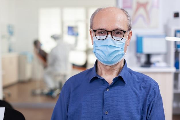 Portret van een oudere man in een tandartspraktijk die op camera kijkt met een gezichtsmasker op een stoel in de wacht...