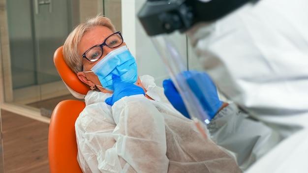 Portret van een oudere patiënt die een beschermingsmasker draagt met pijn in de tanden tijdens de pandemie van het coronavirus in de kliniek. assistent en arts met overall gezichtsschild maskerhandschoenen die vrouw uit tandartsstoel onderzoeken examining