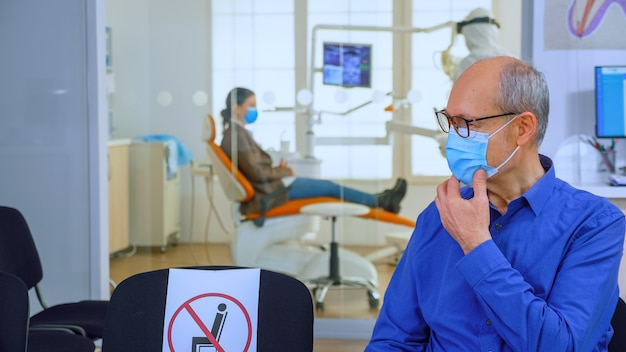 Portret van een oudere patiënt met een beschermingsmasker die op stoelen praat en sociale afstand houdt in de stomatologische kliniek, wachtend op de dokter tijdens het coronavirus. concept van nieuw normaal tandartsbezoek
