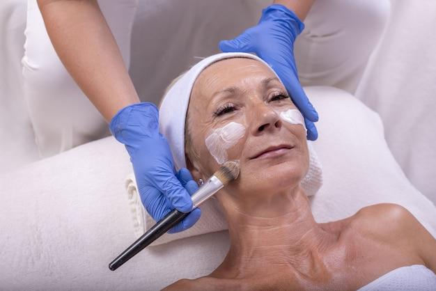 Portret van een oudere vrouw die een anti-verouderingsbehandeling krijgt met dermaroller