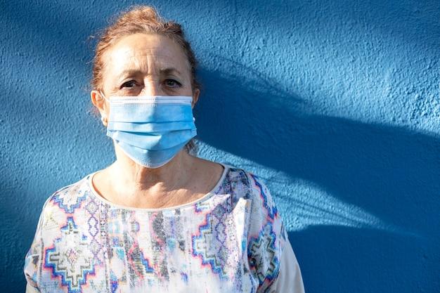 Portret van een oudere vrouw die een gezichtsmasker draagt naast een blauwe muur.