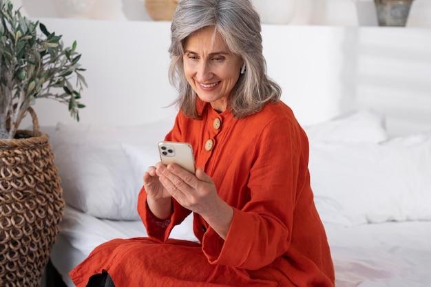 Portret van een oudere vrouw die een smartphone gebruikt