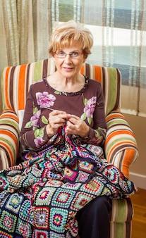 Portret van een oudere vrouw die een vintage wollen quilt breit met kleurrijke patches