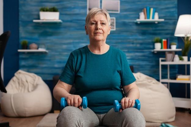 Portret van een oudere vrouw die in de camera kijkt terwijl ze op de zwitserse bal zit en lichaamsspieren traint