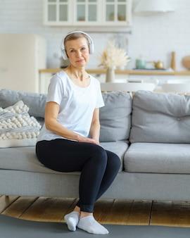Portret van een oudere vrouw die naar de camera kijkt, zit op de bank in een koptelefoon en luistert naar muziek in de woonkamer