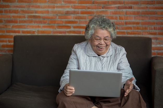 Portret van een oudere vrouw die online zoomvideovergaderingen bekijkt, een gelukkige oudere vrouw van middelbare leeftijd die op de bank zit en een laptop gebruikt tijdens een videogesprek met familievrienden.