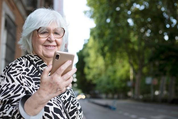 Portret van een oudere vrouw die op straat naar haar mobiele telefoon kijkt