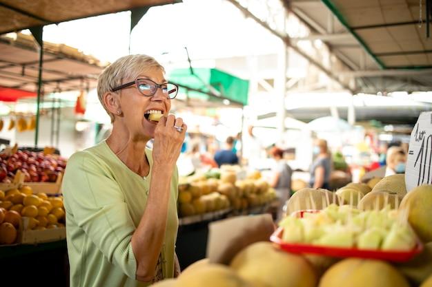 Portret van een oudere vrouw die verse biologische meloen koopt op de markt voor gezonde voeding.