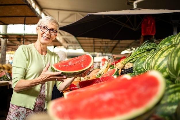 Portret van een oudere vrouw die verse biologische watermeloen koopt op de markt voor gezonde voeding.
