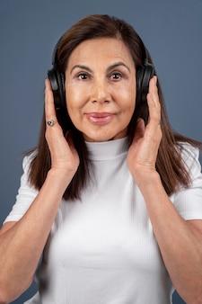Portret van een oudere vrouw die via een koptelefoon naar muziek luistert