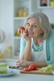 Portret van een oudere vrouw in de keuken