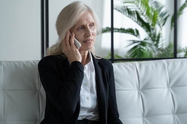 Portret van een oudere vrouw in een pak zittend op een bank en pratend aan de telefoon met een glimlach een oudere vrouw praat op een mobiele telefoon het concept van communicatie en pensioen