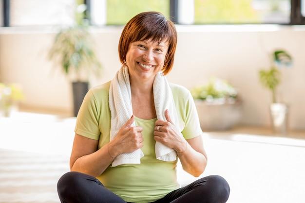 Portret van een oudere vrouw in sportkleding die rust na het sporten binnenshuis of in de sportschool
