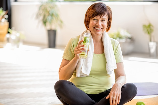 Portret van een oudere vrouw in sportkleding die water drinkt na het sporten binnenshuis, thuis of in de sportschool