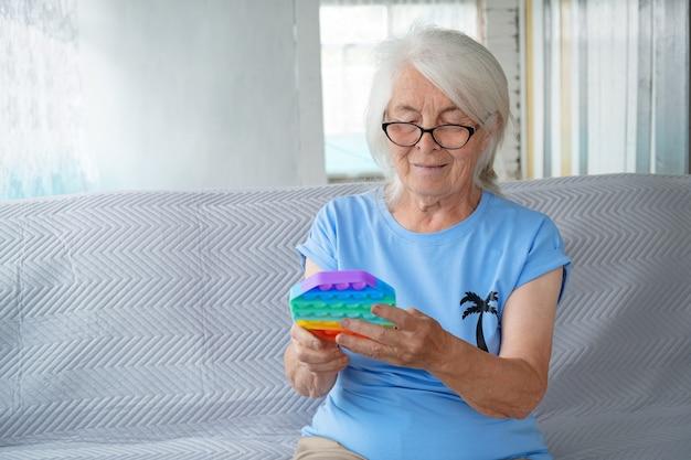 Portret van een oudere vrouw met een bril en grijs haar die op de bank zit en het speelgoed van het kind vasthoudt