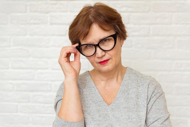 Portret van een oudere vrouw met een bril
