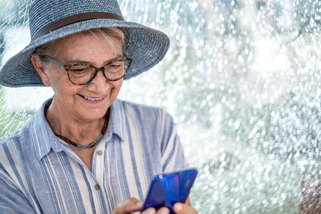Portret van een oudere vrouw met een strohoed die in een winkelcentrum zit en glimlacht en de telefoon gebruikt