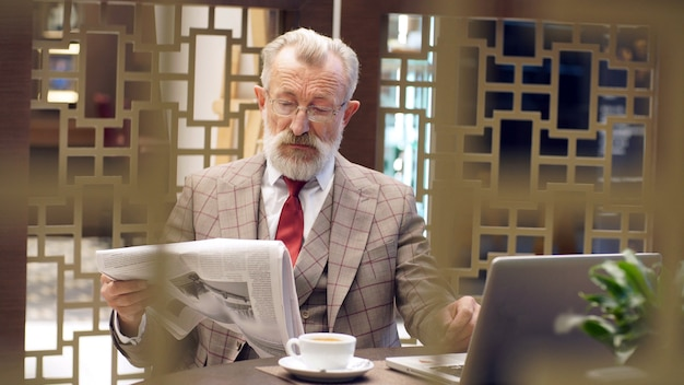 Portret van een oudere, witharige man zittend in een stoel, in de kamer, close-up