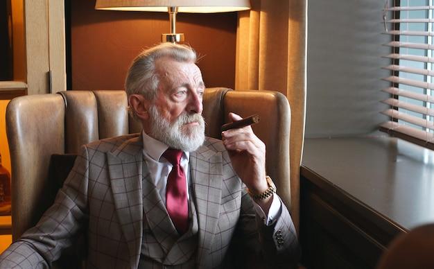 Portret van een oudere zakenman, een oude man in glazen en een stijlvolle formele pak zittend in een stoel op kantoor