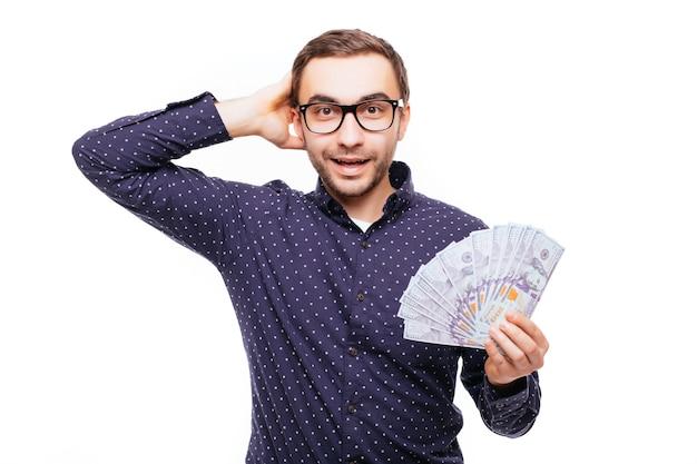 Portret van een overweldigd opgewonden man die een hoop geldbankbiljetten vasthoudt en naar een camera kijkt die over een witte muur is geïsoleerd