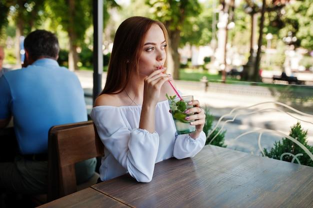 Portret van een overweldigende jonge vrouw die mojitococktail in koffie naast het park drinkt.