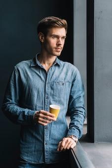 Portret van een overwogen jonge man die wegwerp koffiekopje in de hand te houden