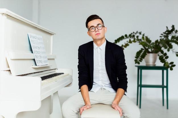 Portret van een overwogen jonge man zit in de buurt van de piano