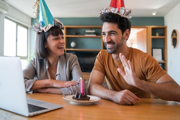 Portret van een paar dat hun verjaardag viert tijdens een videogesprek met een laptop vanuit huis. paar viert verjaardag online in quarantainetijd. nieuw normaal levensstijlconcept.