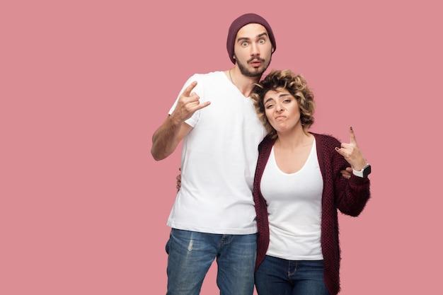 Portret van een paar grappige vrienden in casual stijl die staan, elkaar knuffelen en rock-'n-roll handtekengebaar tonen, kijkend naar de camera. geïsoleerd, binnen, studio-opname, roze achtergrond